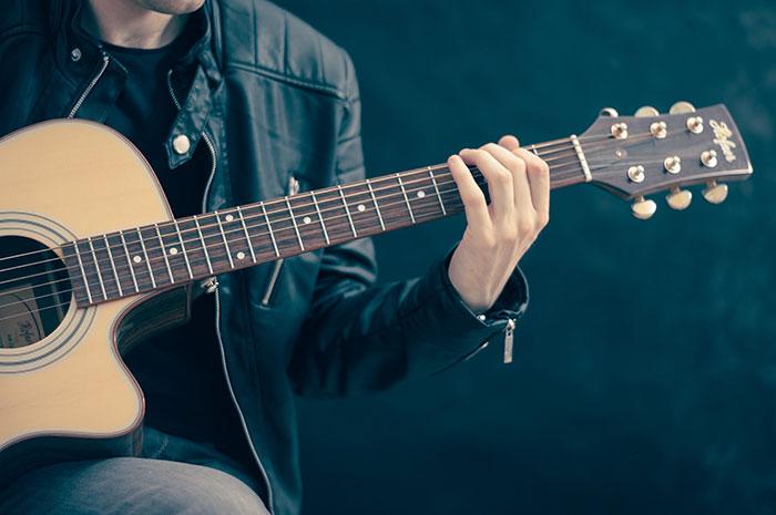 Mies soittaa akustista kitaraa