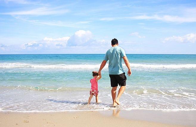 Mies kävelyllä rannalla tyttärensä kanssa. Kuva: Pixabay.com