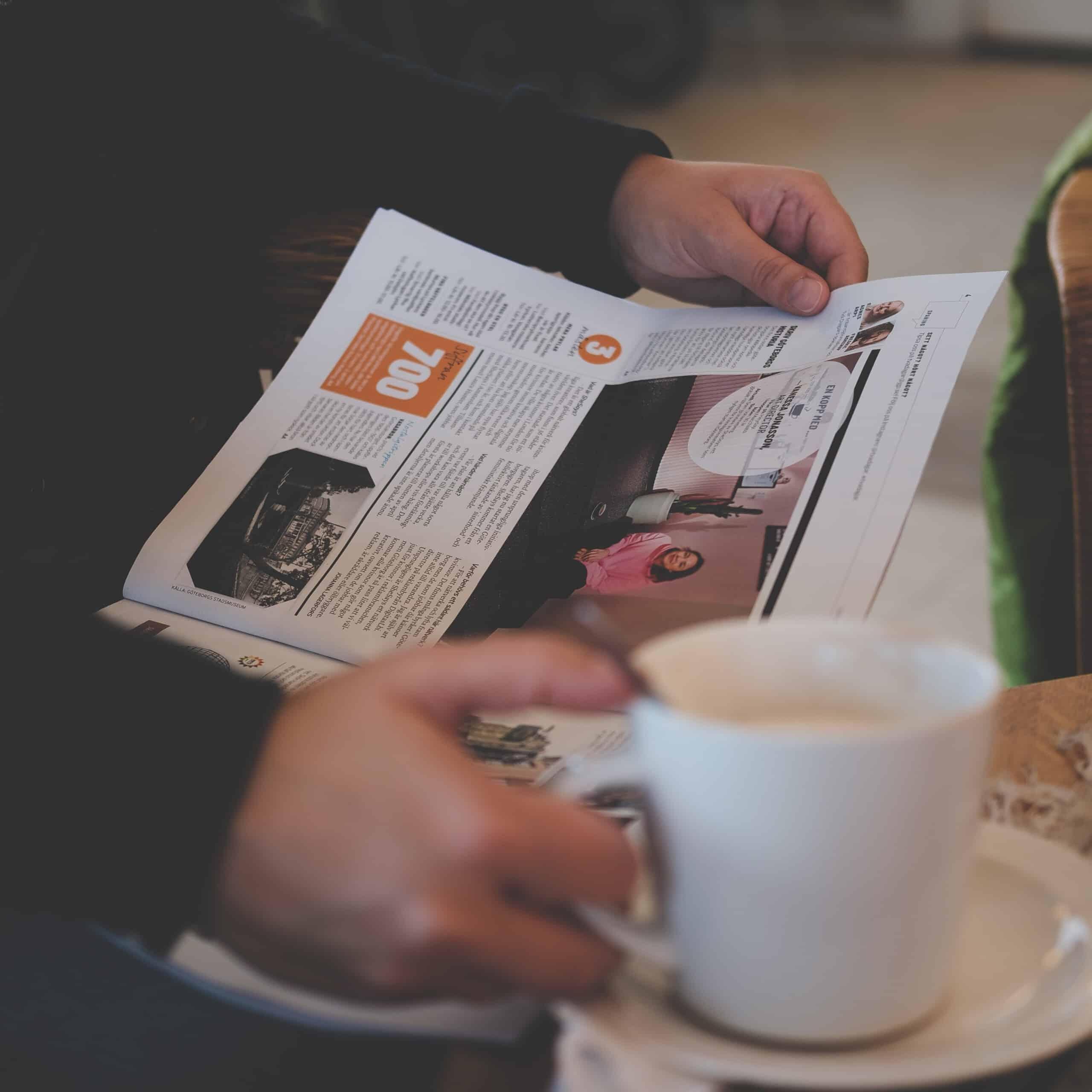 Henkilö lukemassa aikakauslehteä valkoinen kahvimuki kädessään.